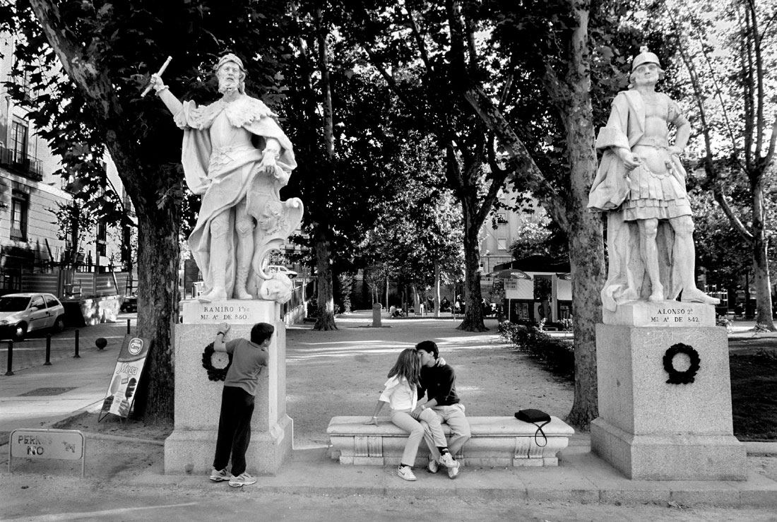 Couple Kissing while kid watches in Madrid Spain